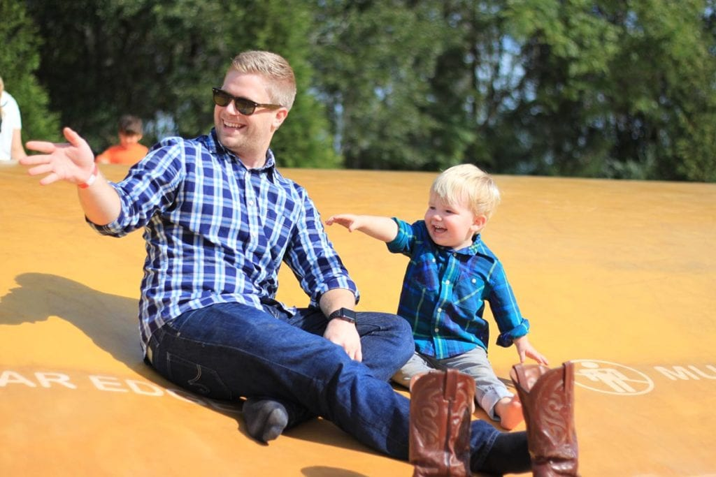 Father and son sitting on a jumping pillow