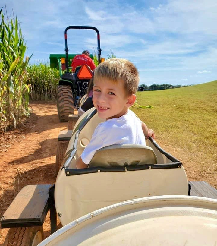 Boy smiling in a tractor pulled train ride