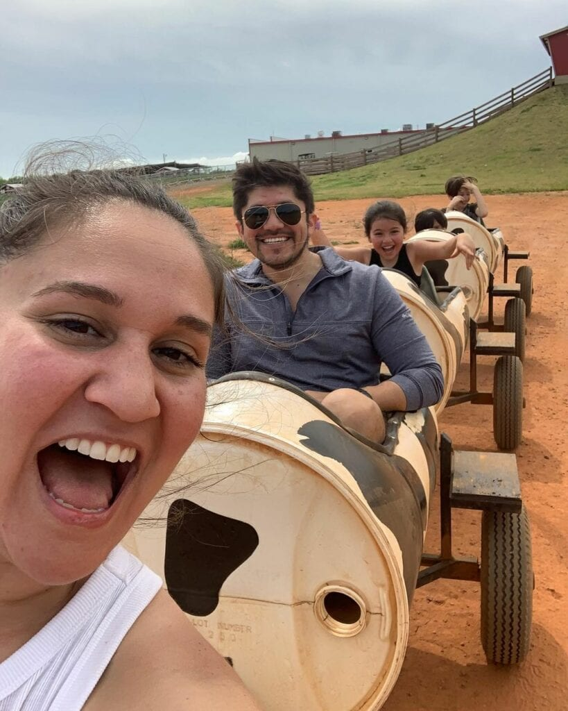 A family laughing on a cow train