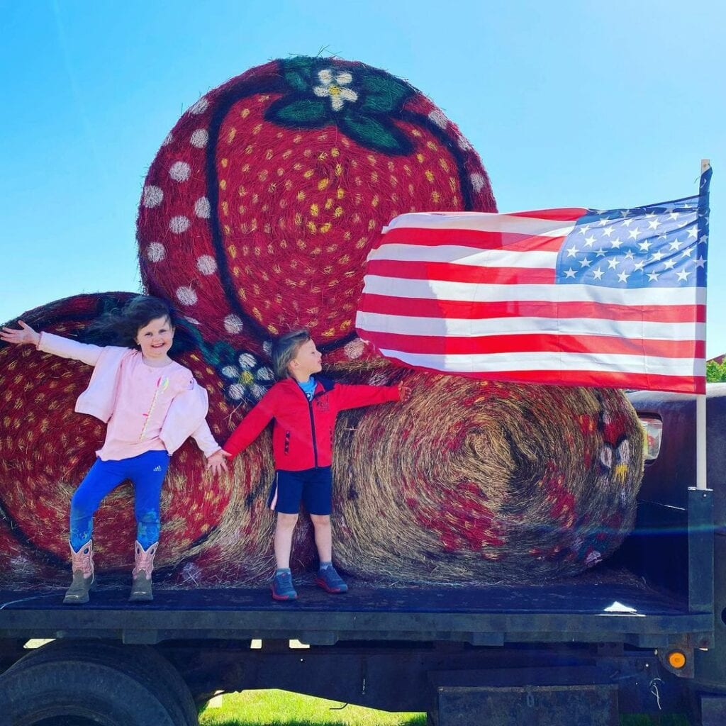 two children on in front of hay bales with American flag