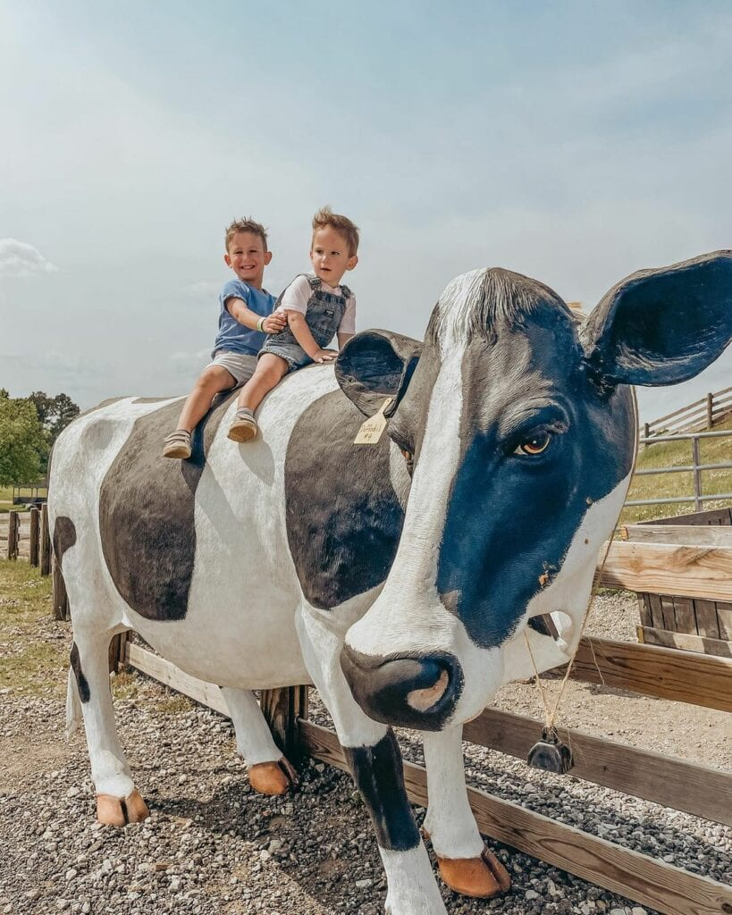 two boys sitting on a cow model