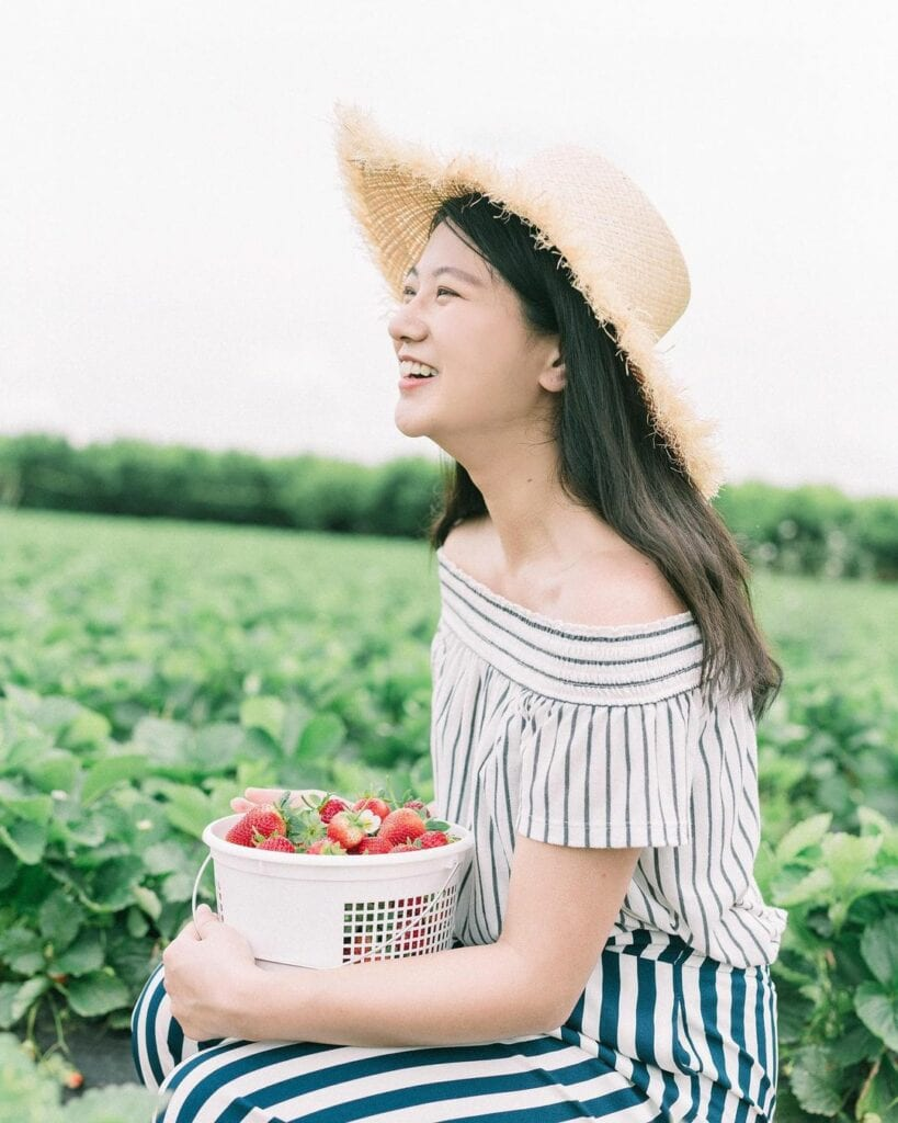 Woman holding a strawberry bucket smiling at farm