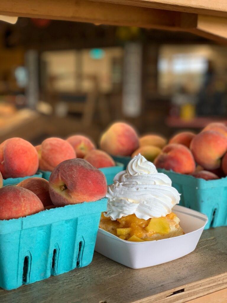 peach cobbler and bins of fresh peaches