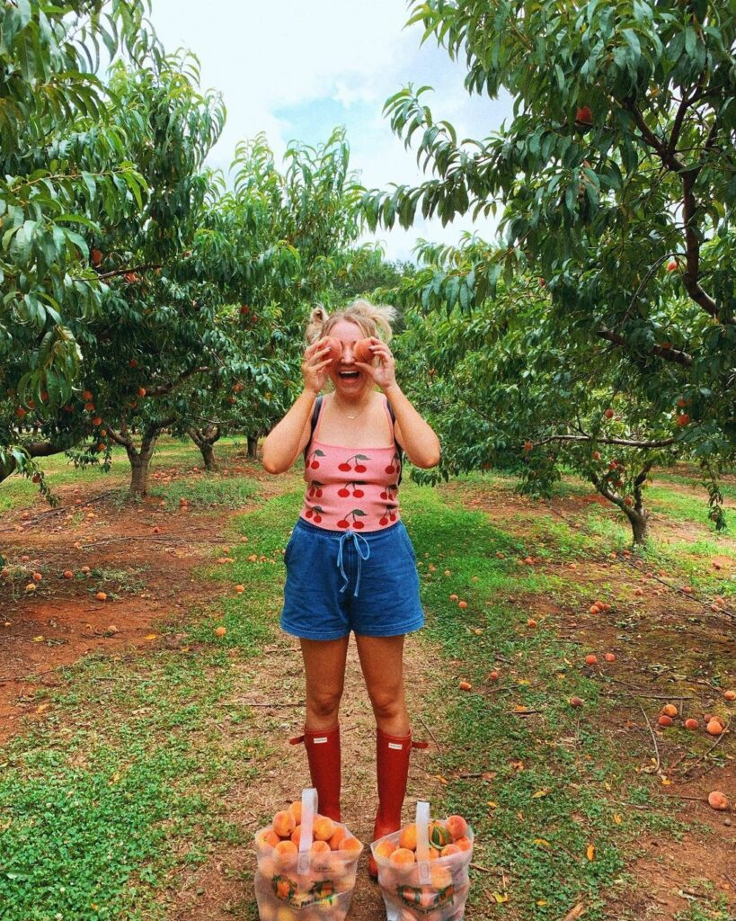 woman holding peaches in front of her eyes at a peach orchard